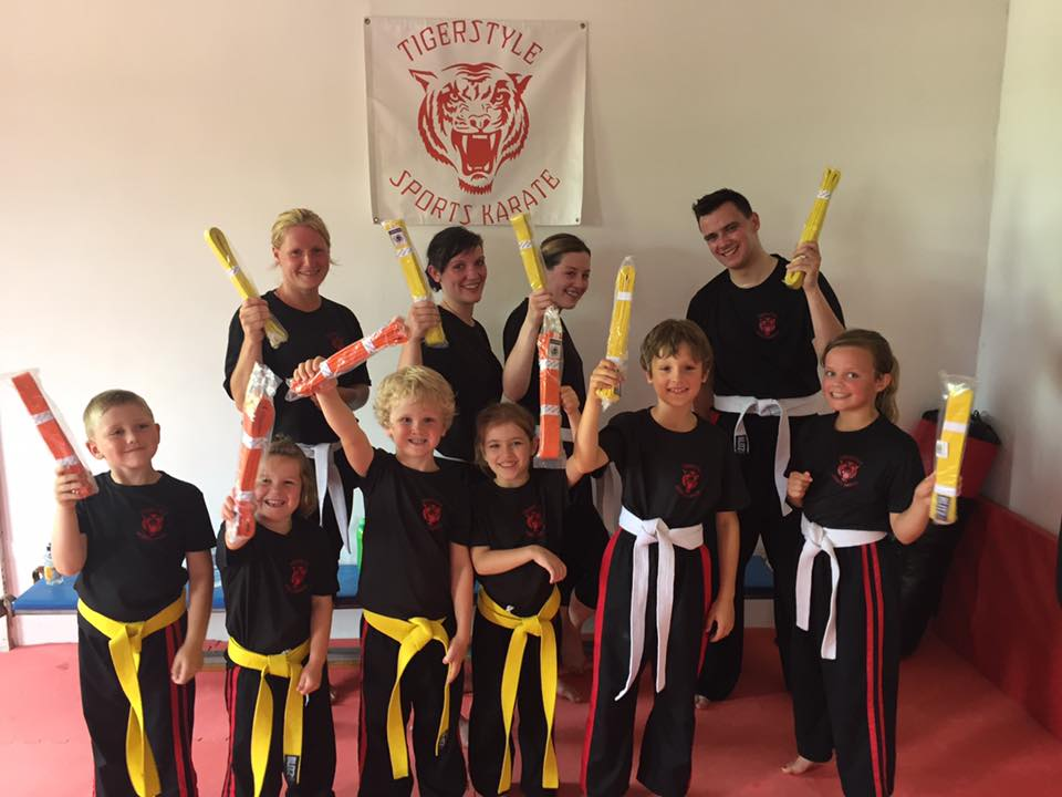 Children and adults after grading with yellow and orange belts